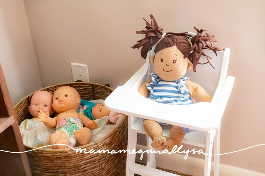 a basket full of baby dolls and a white baby doll highchair with a doll sitting in it