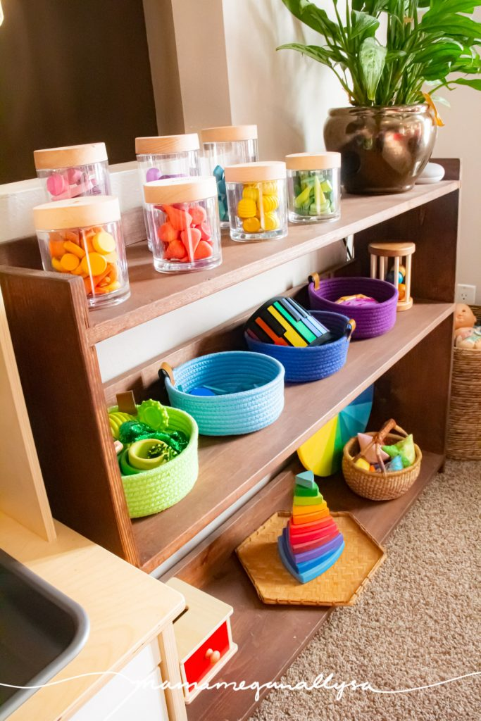 a toy shelf in our livingroom playroom, a rainbow of loose parts jars on the top shelf, colorful rope baskets on the second and other rainbow toys on the bottom shelf