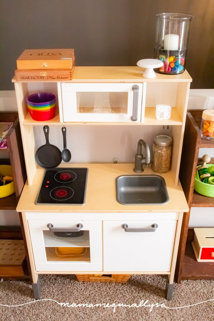 an ikea play kitchen with a few little rainbow touches