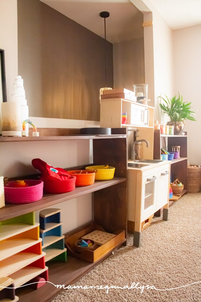 a toy shelf in our livingroom playroom, colorful rope baskets on the second and other rainbow toys on the bottom shelf