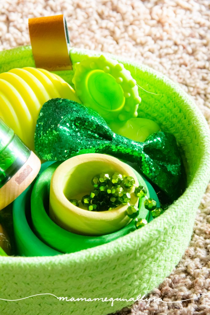 a close up of our green discovery basket filled with gree treasures and baby toys