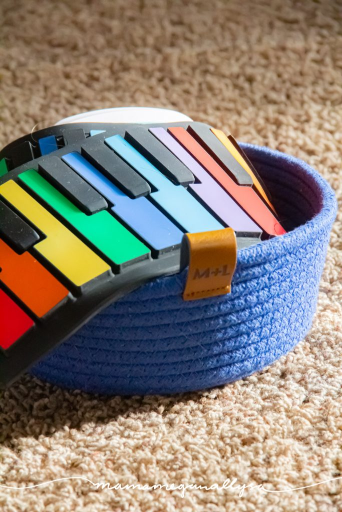 a close up of our rainbow roll up piano in a blue rope basket