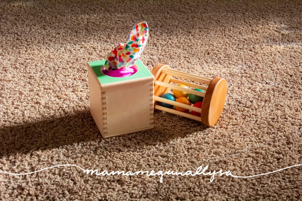 a couple of baby toys on the floor a Lovevery tissue box and a wooden cylinder rolling rattle