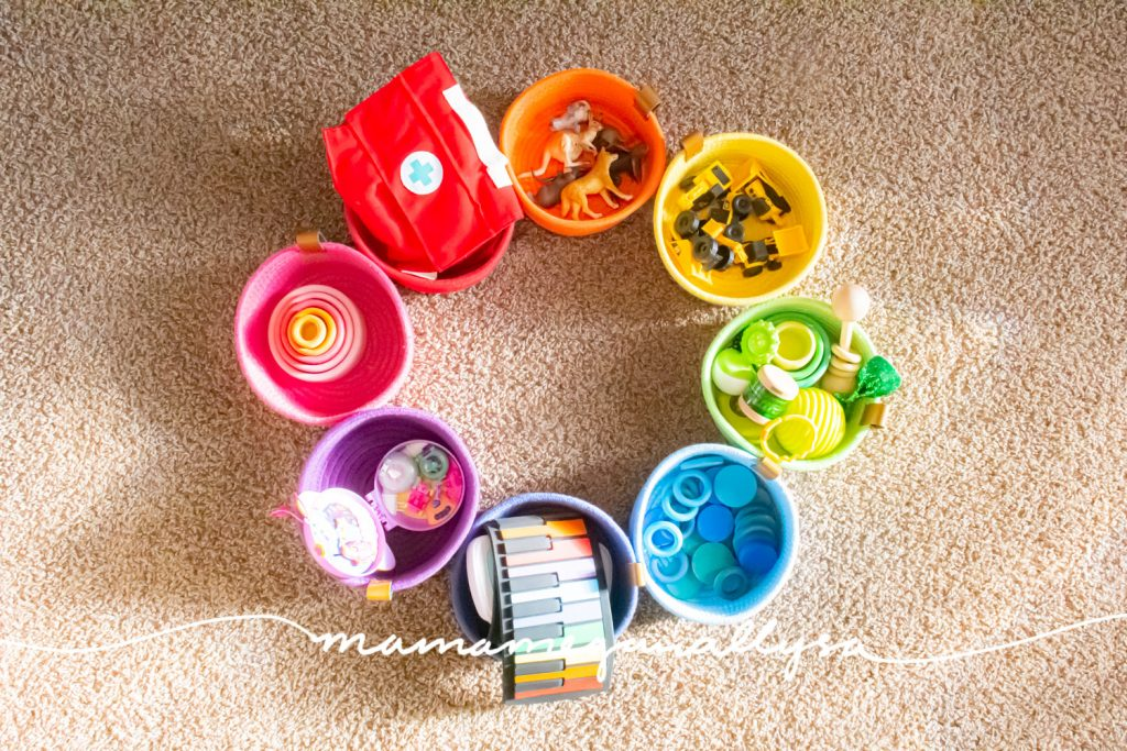 a rainbow of rope baskets filled with toys arranged as a circle on the floor