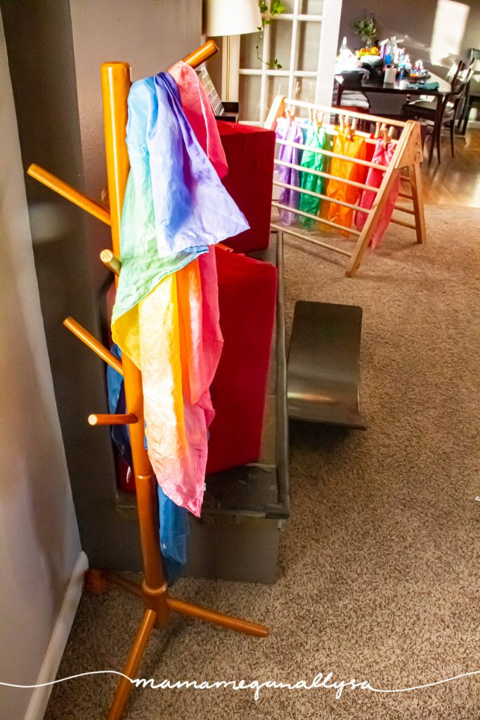 a kids tree stand with our rainbow play silk hanging on it with our pikler triangle in the background with the rest of our play silks  hanging