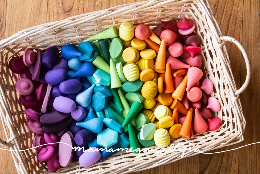 a top down shot of my custom wooden loose parts arranged in a wicker basket in rainbow order