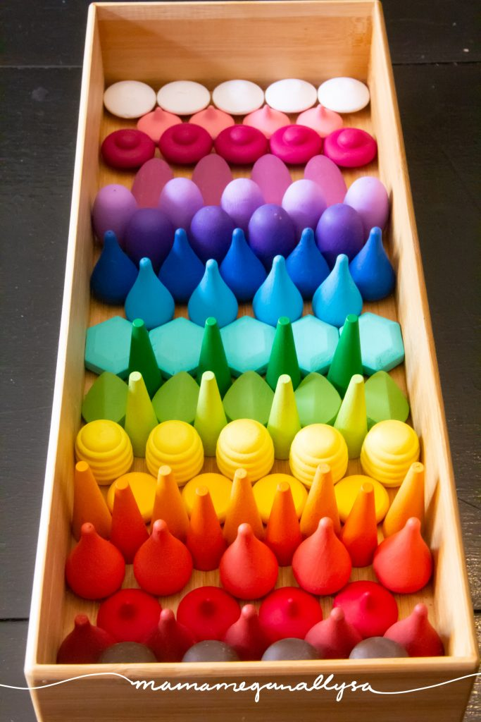 a wooden tray filled with a pattern of wooden loose parts in rainbow order