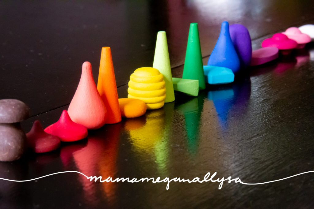 a long line of wooden loose parts all painted and arranged in ROYGBIV order on a black table