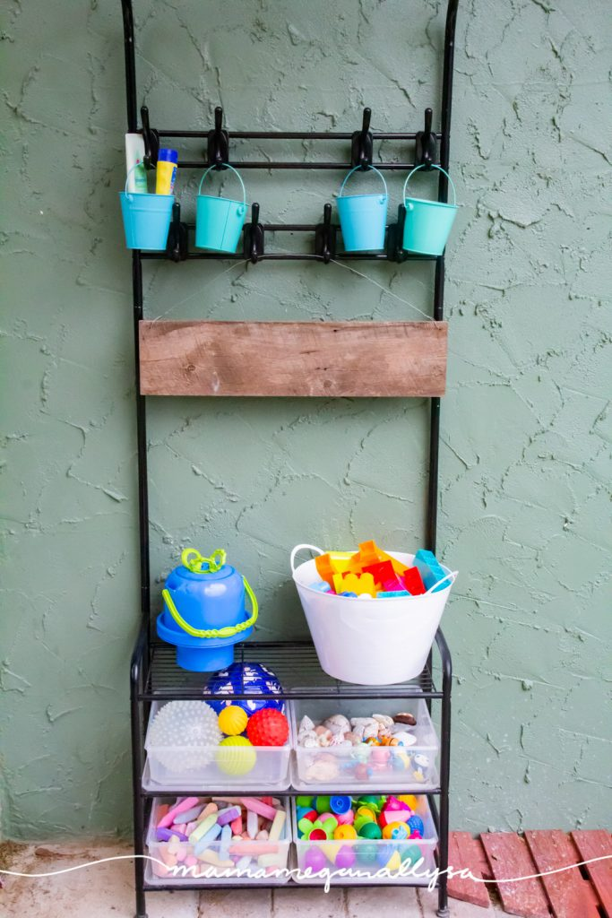 our backyard toy shelf is a black metal coat tree with teal buckets hanging from the hooks and plastic bins and buckets on the lower shelves full of outdoor toy rotation toys