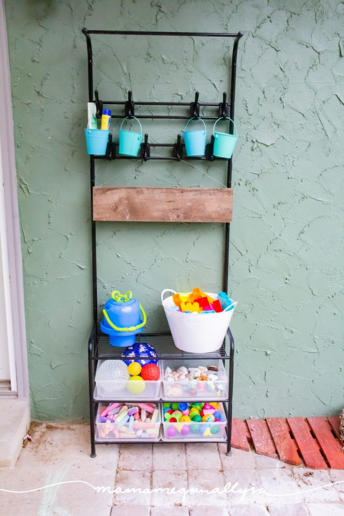 out backyard rack full of toys for our outdoor toy rotation with buckets hanging on the hooks up high and baskets and bins on the lower shelves