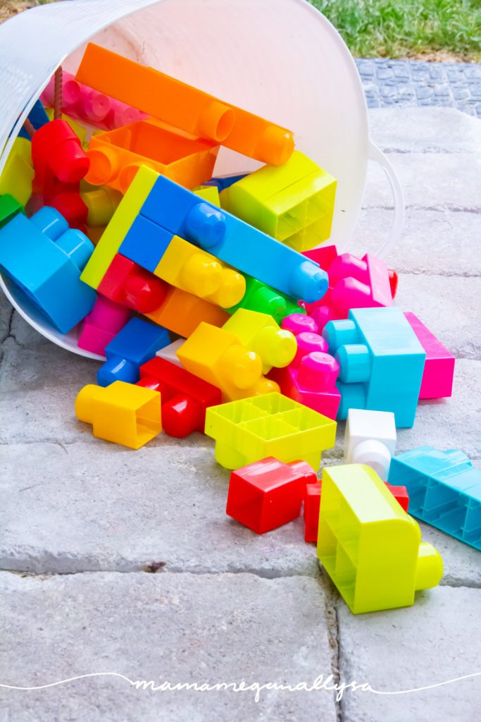 some Megablocks spilling out of a bucket on the patio in the back yard