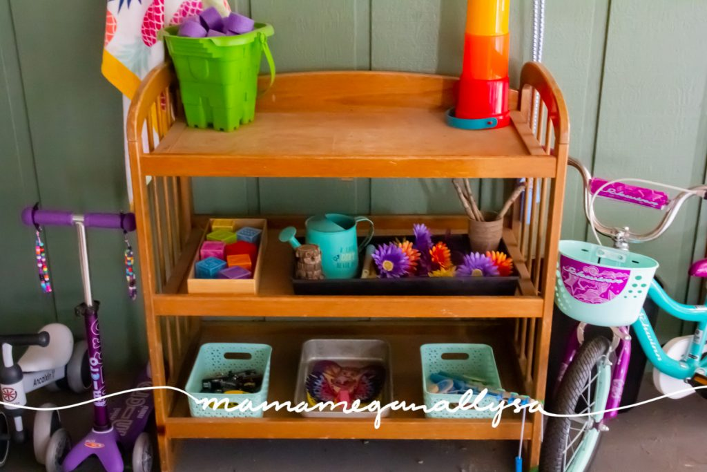 wooden diaper changing table holds baskets and trays of toys for out outdoor toy rotaion