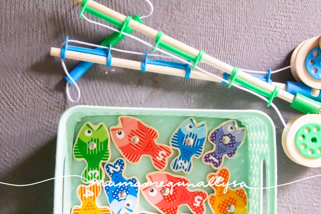 magnetic fishing game and poles in a teal bin on the porch