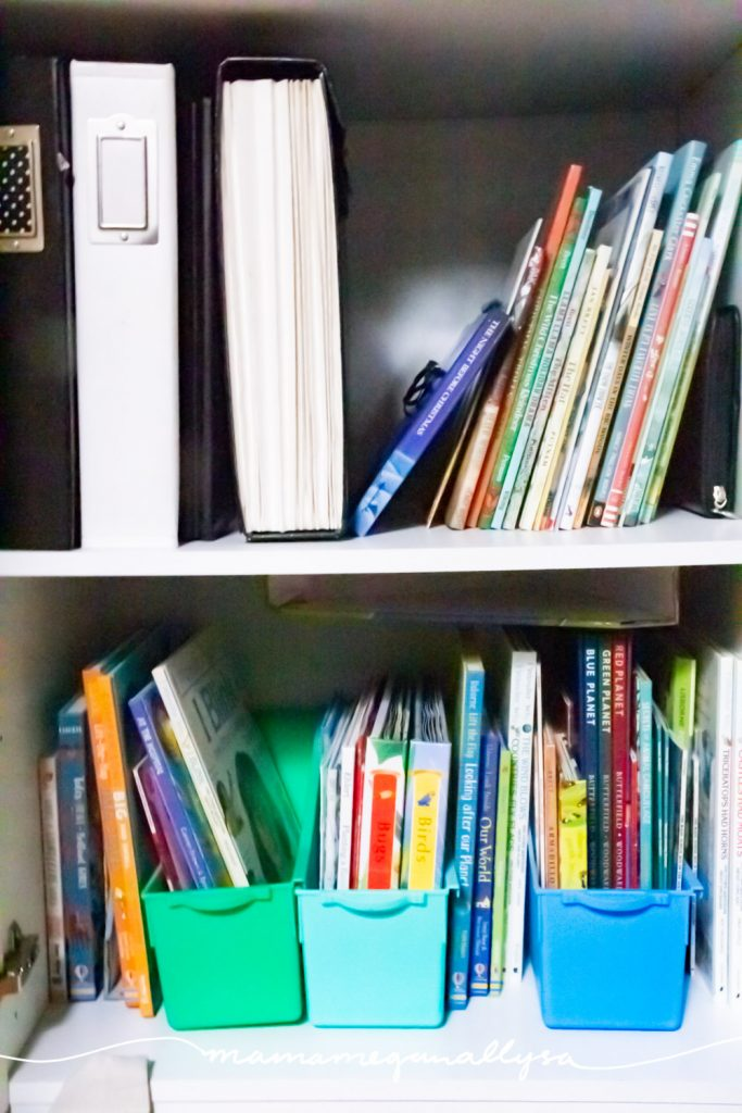 a storage cabinets bottom two shelves with various homeschool books and unit study books