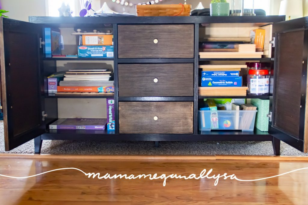 a sofa cabinet with two cabinet doors open and filled with homeschool materials and puzzles